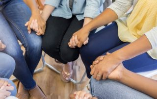 A group of people seated in a circle holding hands.